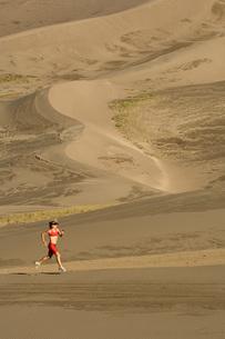 Woman running on sand dunesの写真素材 [FYI01997053]