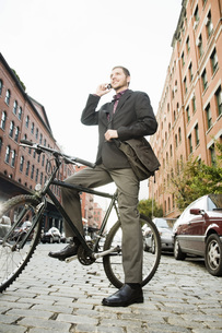 Man on bicycle talking on cell phoneの写真素材 [FYI01997076]
