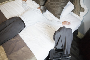 Businessman laying on bedの写真素材 [FYI01997077]