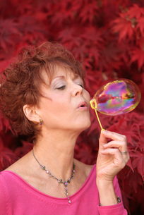 Woman blowing bubbles in parkの写真素材 [FYI01997086]
