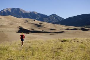 Woman running on sand dunesの写真素材 [FYI01997099]