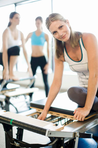 Portrait of smiling woman sitting on pilates equipmentの写真素材 [FYI01997120]