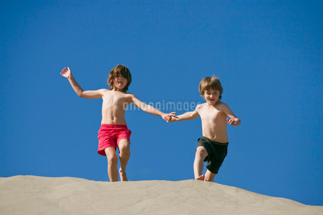 Boys holding hands and running down sand duneの写真素材 [FYI01997128]