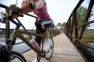 Woman riding bicycle over footbridgeの写真素材 [FYI01997164]