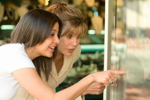 Hispanic woman and daughter window shoppingの写真素材 [FYI01997181]