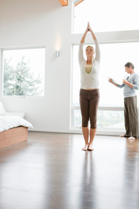 Woman standing in yoga pose and man reading newspaperの写真素材 [FYI01997196]