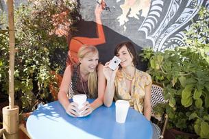 Young women looking at digital cameraの写真素材 [FYI01997230]