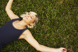 Woman laying in grassの写真素材 [FYI01997271]