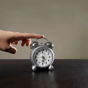 Hand on alarm clockの写真素材 [FYI01997311]