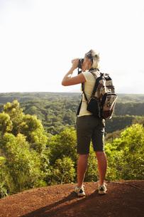 Woman looking through binocularsの写真素材 [FYI01997314]