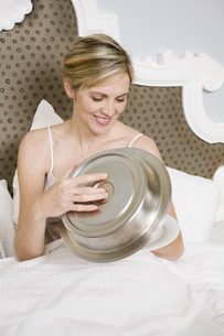 Woman holding room service plate in bedの写真素材 [FYI01997333]