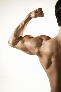 Bare-chested man flexing biceps musclesの写真素材 [FYI01997334]