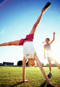 Girls doing cartwheels in sunlightの写真素材 [FYI01997377]