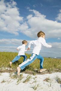 Boys running on beachの写真素材 [FYI01997391]