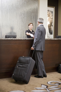 man checking in at hotel front deskの写真素材 [FYI01997398]