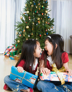 Asian sisters opening Christmas presentsの写真素材 [FYI01997421]