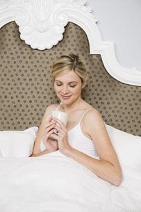 Woman holding coffee mug in bedの写真素材 [FYI01997437]