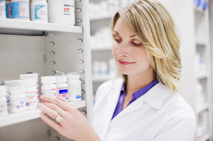 Close up of pharmacist looking at pill bottles on shelfの写真素材 [FYI01997440]