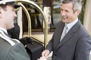 Businessman tipping bellhopの写真素材 [FYI01997465]