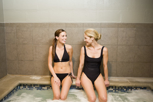 Two women sitting on edge of hot tubの写真素材 [FYI01997482]