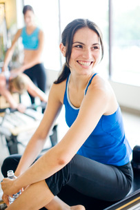 Smiling woman sitting on pilates equipmentの写真素材 [FYI01997484]