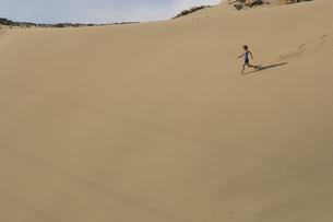 Person running down sand duneの写真素材 [FYI01997501]
