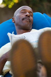 African man sleeping with newspaperの写真素材 [FYI01997503]