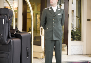 Bellhop standing next to luggage cartの写真素材 [FYI01997507]