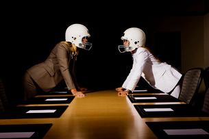 Businesswomen in face-off wearing football helmetsの写真素材 [FYI01997513]