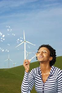 African woman blowing bubbles near wind generatorsの写真素材 [FYI01997528]