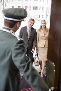 Bellhop opening door for coupleの写真素材 [FYI01997571]