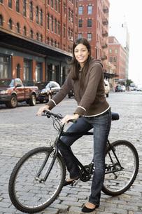 Hispanic woman standing with bicycleの写真素材 [FYI01997595]