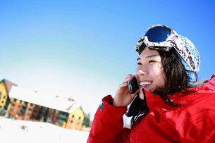 Asian skier talking on cell phoneの写真素材 [FYI01997596]