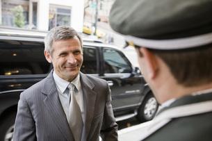 Businessman smiling at bellhopの写真素材 [FYI01997610]