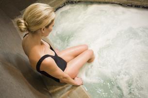 Woman sitting on edge of hot tubの写真素材 [FYI01997625]