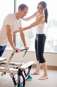 Personal trainer guiding man on pilates equipmentの写真素材 [FYI01997635]