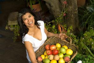 Woman carrying basket of fruitの写真素材 [FYI01997637]