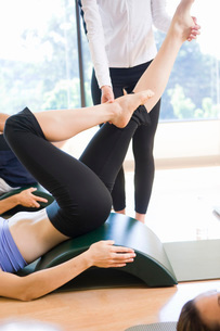 Instructor guiding womanis raised legs in exercise classの写真素材 [FYI01997646]