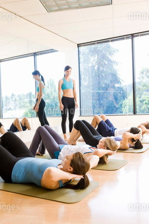 People in exercise class doing sit-upsの写真素材 [FYI01997647]
