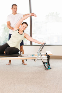Personal trainer guiding woman on pilates equipmentの写真素材 [FYI01997650]