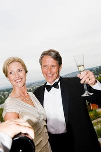 Couple in eveningwear drinking champagne on balconyの写真素材 [FYI01997651]