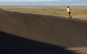 Woman running on sand dunesの写真素材 [FYI01997663]