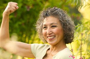 Asian woman flexing biceps in gardenの写真素材 [FYI01997676]