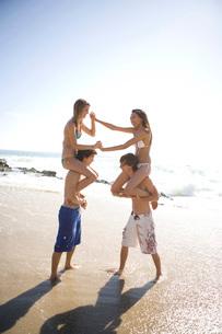 Multi-ethnic couples chicken fighting on beachの写真素材 [FYI01997681]