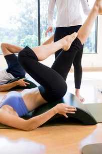 Woman with legs raised in exercise classの写真素材 [FYI01997684]