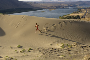 Woman running down sand duneの写真素材 [FYI01997692]