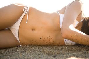 Asian woman in bikini laying on beachの写真素材 [FYI01997716]