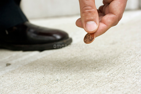 Close up of man picking up penny from streetの写真素材 [FYI01997718]
