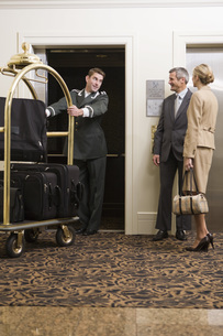 Bellhop pulling luggage cartの写真素材 [FYI01997719]