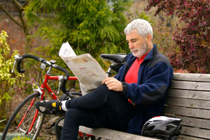 Man with bicycle reading newspaper in parkの写真素材 [FYI01997721]